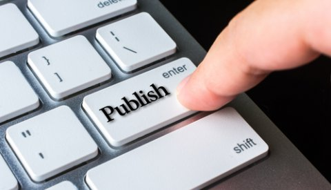 Finger pushing the publish button