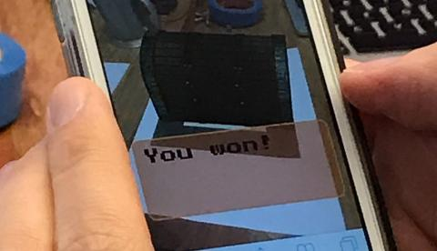 "A close-up of a phone using the AR treasure hunt app, showing the text ""You Won!"""