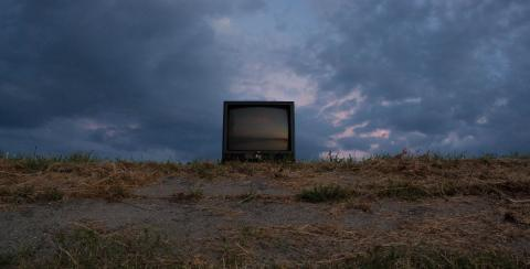 TV sitting in field with dark clouds