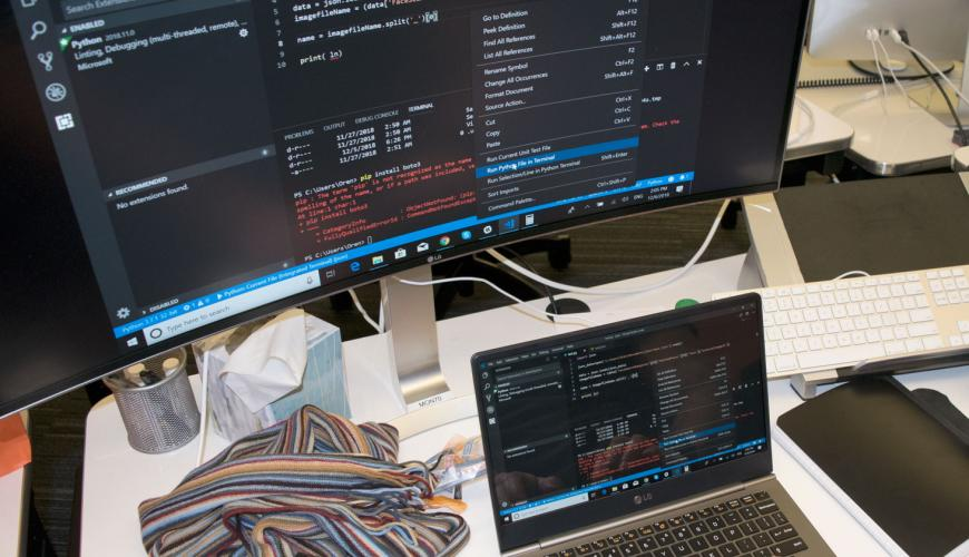 A large computer monitor showing code, above a laptop where hands are typing code
