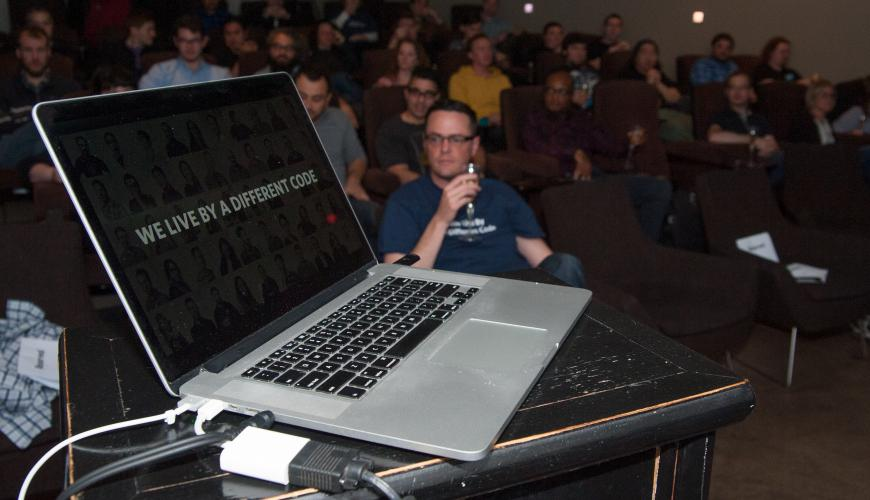 laptop with audience in background