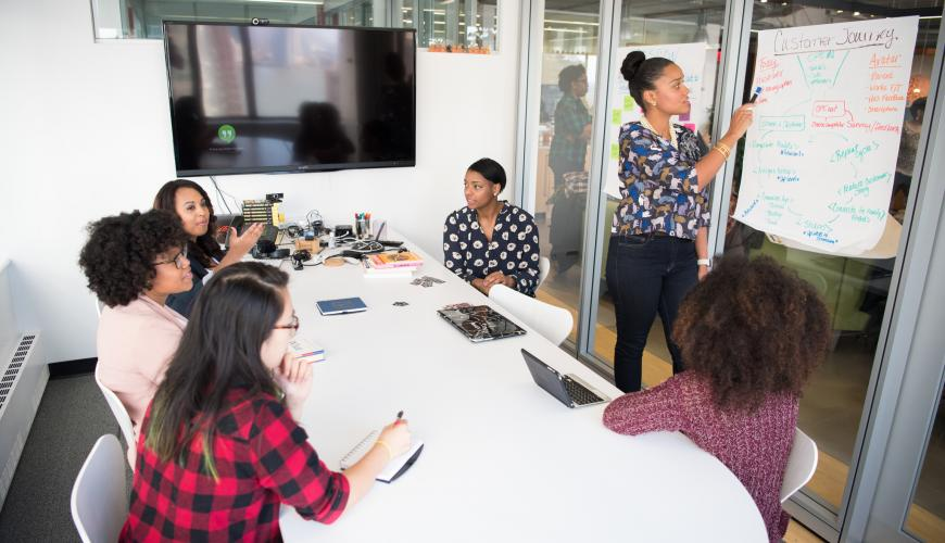 Several engineers of color in a business meeting. Confident and assured, they are discussion how to create the best customer journey for the amazing product.