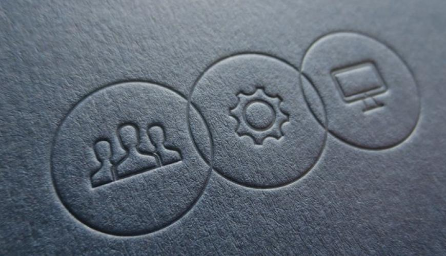 embossed graphic on paper of people, a cog, and a computer screen